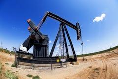 Ouvrier chargé des pompes de puits de pétrole. Photographie stock libre de droits