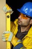 Ouvrier contrôlant le niveau vertical Photos stock