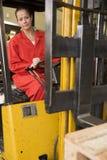 Ouvrier d'entrepôt dans le chariot élévateur Images stock