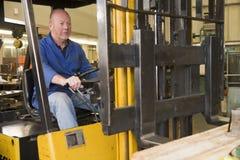Ouvrier d'entrepôt dans le chariot élévateur Photo stock