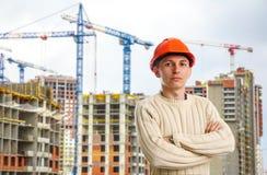 Ouvrier dans le casque rouge sur le fond des bâtiments Image libre de droits