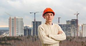 Ouvrier dans le casque rouge sur le fond des bâtiments Photos stock