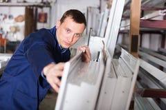 Ouvrier de fabrication avec des fenêtres de PVC Photos libres de droits