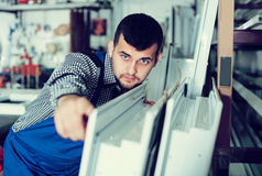Ouvrier de fabrication avec des fenêtres de PVC Images stock