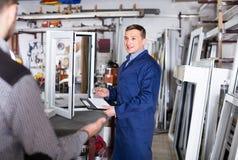Ouvrier de fabrication dans la combinaison démontrant la fenêtre différente de PVC Photos stock
