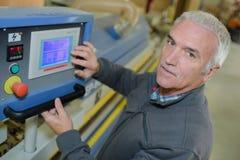 Ouvrier de fabrication manipulant les dispositifs démontables dans l'usine photographie stock