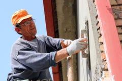 Ouvrier de maçon plâtrant le mur Photos libres de droits