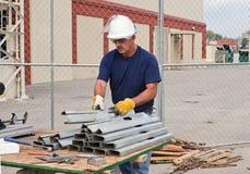 Ouvrier empilant des goujons en métal photos stock