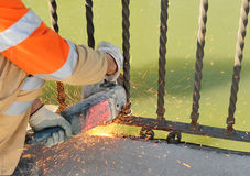 Ouvrier en coupant le fer avec une machine électrique Photo stock