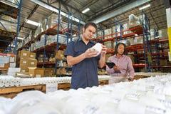 Ouvrier et gestionnaire contrôlant des marchandises sur la chaîne de production photos libres de droits