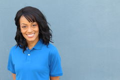 Ouvrier féminin d'afro-américain posant dans le croisement uniforme d'isolement sur le bleu Photographie stock