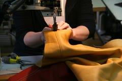 Ouvrier féminin sur la coudre-machine ouvrant le cuir Photographie stock
