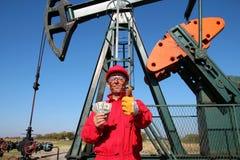 Ouvrier heureux de pétrole avec de l'argent et la pompe Jack Photos libres de droits
