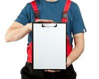 Ouvrier industriel dans la planchette uniforme de fixation image stock