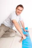 Ouvrier installant un plancher stratifié Photographie stock libre de droits