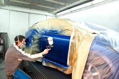 Ouvrier peignant un véhicule. Photo stock
