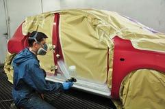 Ouvrier peignant un véhicule. Image stock