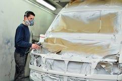 Ouvrier peignant un véhicule. Photographie stock libre de droits