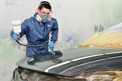 Ouvrier peignant un véhicule. Image libre de droits