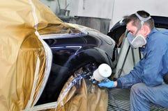 Ouvrier peignant une voiture. Photographie stock