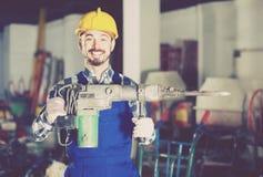Ouvrier pratiquant ses qualifications avec le foret pneumatique au worksh Images stock