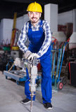 Ouvrier pratiquant ses qualifications avec le foret pneumatique au worksh photographie stock