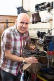 Ouvrier réparant des paires de chaussures Photo stock