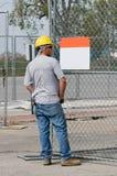 Ouvrier regardant le signe blanc Images stock