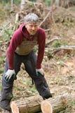 Ouvrier se reposant en arrière du bois de levage Photographie stock