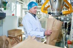 Ouvrier supérieur Working à la ligne d'emballage photographie stock libre de droits