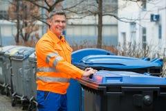 Ouvrier tenant la poubelle proche sur la rue Images stock