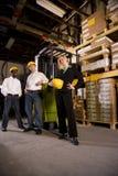 Ouvriers avec le bossage femelle dans l'entrepôt de mémoire Photographie stock libre de droits