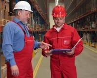 Ouvriers contrôlant la facture Photo stock
