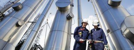 Ouvriers de pétrole et de gaz avec des canalisations Photographie stock libre de droits