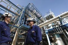 Ouvriers et raffinerie de pétrole Photographie stock libre de droits