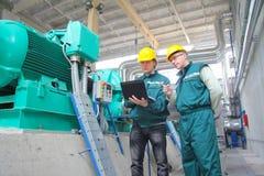 Ouvriers industriels avec le cahier Photo stock