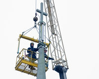 Ouvriers installant une antenne de téléphone portable sur l'église Images libres de droits