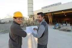 Ouvriers regardant des plans sur le chantier images stock