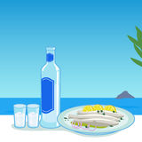 Ouzo and fish in Greece. A bottle of ouzo and cooked fish in a tavern table next to the sea Royalty Free Stock Image