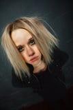 Ovårdad flicka som poserar på svart bakgrund Fotografering för Bildbyråer
