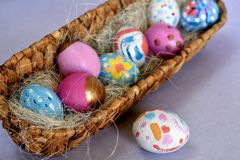 Oval basket full of brightly colored Easter eggs with one white spotted egg beside stock photo