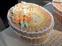 Oval cream-coloured handicraft paper box decorated with roses. Oval cream-coloured wickerwork box from paper decorated with roses royalty free stock photography