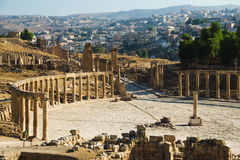 Oval Forum and long colonnaded street or cardo ancient Greco-Roman city Gerasa. Modern Jerash on background. Tourism industry, tou Stock Images