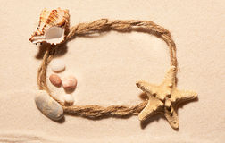 Oval frame of rope, starfish, seashell and stones on sand Royalty Free Stock Photos