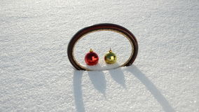 Oval frame and two Christmas balls on winter snow Royalty Free Stock Images