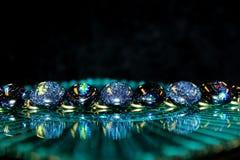 Oval glass cabochon bracelet reflected on a glass plate. An oval glass cabochon bracelet is reflected on a glass plate Stock Photography