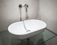 Oval hand wash basin. White ceramic hand wash basin of oval shape on glass shelf Royalty Free Stock Image