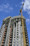Oval high-rise building. In gray and yellow construction crane Royalty Free Stock Images
