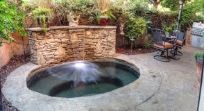 Oval hot tub spa with waterfall and feng shui garden decor. Irvine, CA, USA – August 19, 2016: Oval hot tub spa with waterfall and feng shui garden decor Stock Image