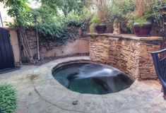 Oval hot tub spa with waterfall and feng shui garden decor Stock Photography